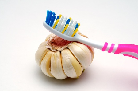 bad hygiene: Toothbrush and garlic on a white background