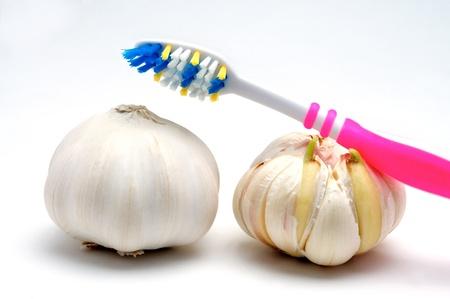 Cepillo de dientes y el ajo en un fondo blanco Foto de archivo