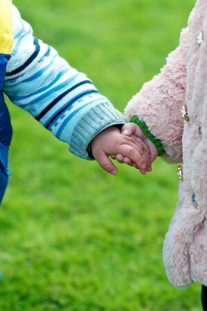 Two Children holding each others hands in the nature