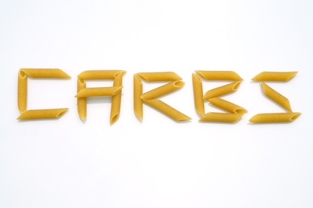 Rigatoni Pasta pieces form the word carbs as carbohydrates on white background.