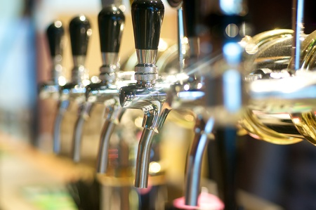 silver bar: Beer taps in a row