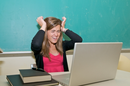 Stressed out college student studying in classroom with laptop