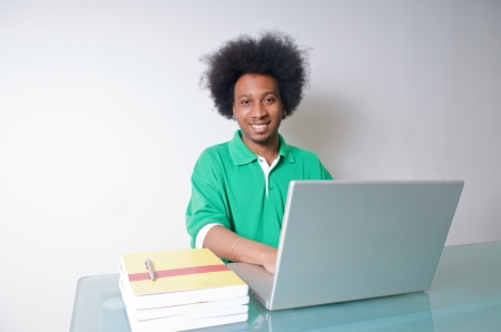 African American student in green Shirt with latop and textbooks photo