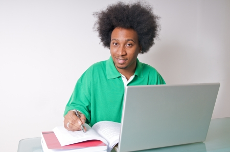African American student studying with latop and textbooks photo