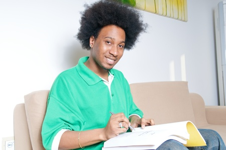 African American teenager studying in livingroom photo