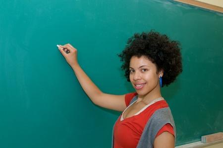 African American student writing on blackboard in classroom