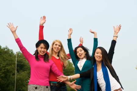 Group of 4 female students outdoor cheering photo