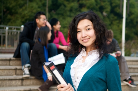 Asian Student with notepad on campus photo