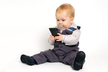 beb� rubio en traje de mensajes de texto con el tel�fono m�vil Foto de archivo