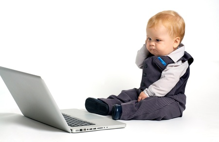 Bambino biondo in tuta di lavoro con il computer portatile e di pensare Archivio Fotografico - 15115886