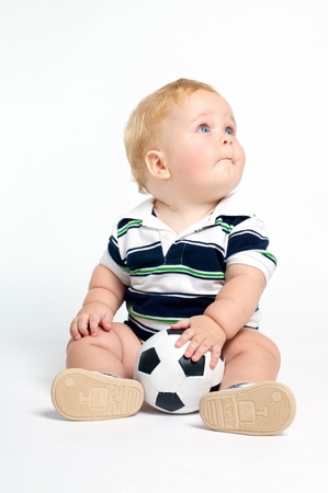 the infancy: Fun blond baby with blue eyes playing with soccer ball Stock Photo