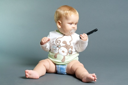 the infancy: blond baby playing with a marker