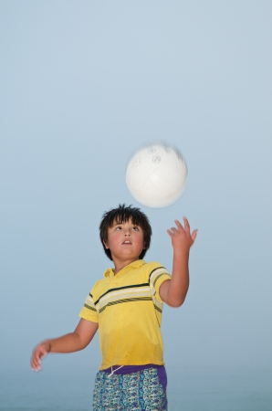 Asian kid standing on the beach playing volleyball Stock Photo