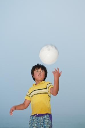 Chico asi�tico de pie en la playa jugando voleibol Foto de archivo