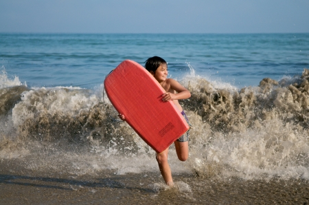 boogie: Boy running on the beach with a boogie board Stock Photo