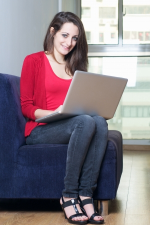 Beautiful girl sitting on a sofa with her wireless laptop photo
