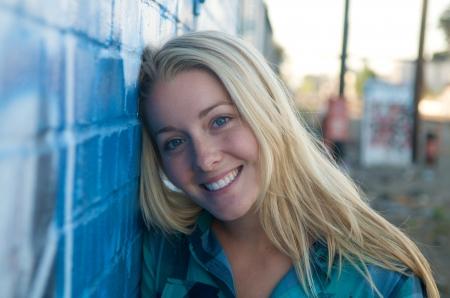 rubia ojos azules: Una muchacha sonriente rubia y una pared de graffiti Foto de archivo
