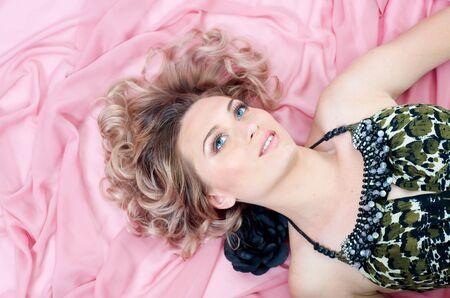 perm: Blond Caucasian woman in pink silk background