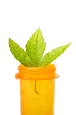 leaf on a pill bottle as alternative medicine concept