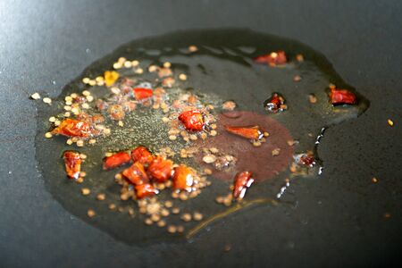 Frying spicy chilly pepper in oil in a wok Banco de Imagens
