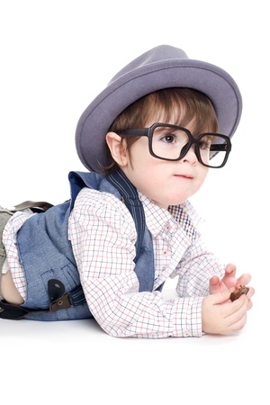 Cute smart baby kid with hat and glasses eating chocolate