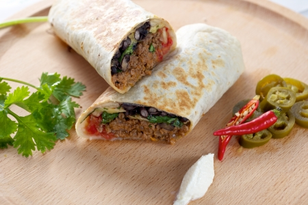 Beef Burrito on wooden board with red chillies peppers  photo