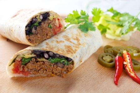 Beef Burrito on wooden board with red chillies peppers  Stock Photo