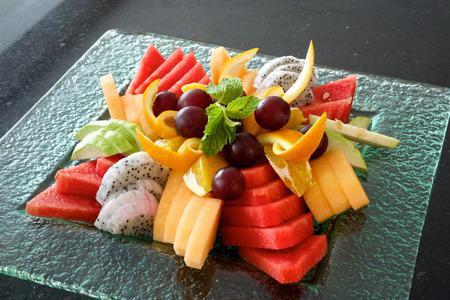 수박, 멜론, 포도, 오렌지, 드래곤 과일, 민트와 함께 다채로운 여름 과일 플래터