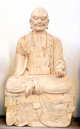 chinese philosophy: Wooden Buddha in prayer over white  Stock Photo