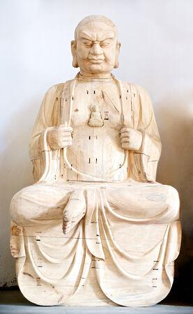 tallado en madera: Buda de madera en la oración sobre blanco