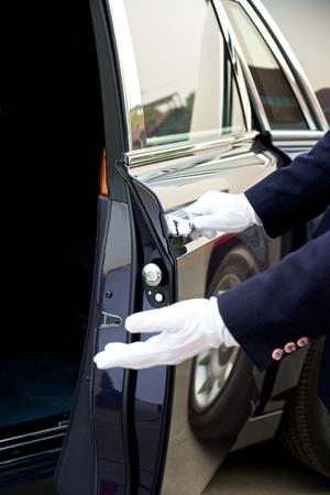 puertas abiertas: Chofer abre la puerta del coche Foto de archivo