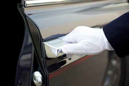 Chauffeur opent autodeur Stockfoto