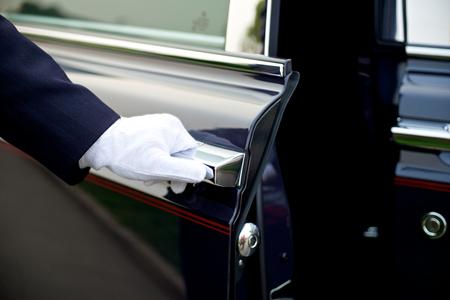 Servicio de lujo con chofer abre la puerta