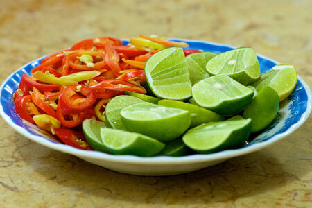 Plate with green limes and red hot chilly peppers in Vietnam