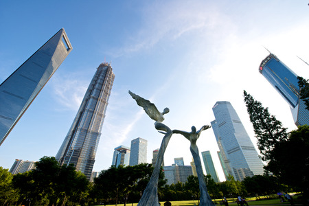 jin mao tower: Shanghai, China - July 22, 2014: A beautiful view of Shanghai tallest building at the century park with sculptures. Editorial