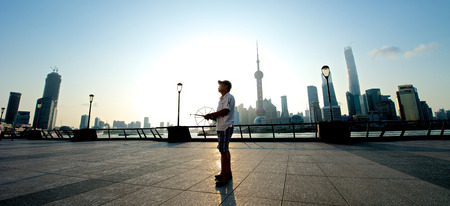 jin mao tower: Shanghai, China - August 6, 2014: A beautiful view of Shanghai Skyline at sunrise with man flying kite.