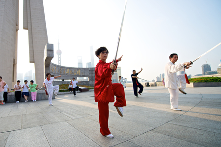 tai chi: Shanghai, China - August 6, 2014: A beautiful view of Shanghai Skyline at sunrise with people doing Tai Chi.  Editorial