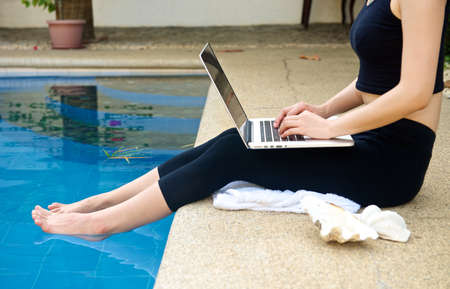 working on computer: Girl with Laptop by the pool, working on vacation with mobility concept Stock Photo
