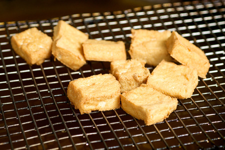 Stinky tofu on a metal oil screen photo