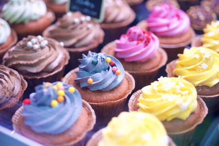 candy store: Colorful cupcakes in window display in store