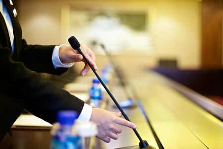 speaker: Person preparing microphone in conference room Stock Photo