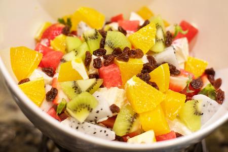 ensalada de frutas: Ensalada deliciosa de la fruta con la sandía, naranjas, kiwi y uvas pasas