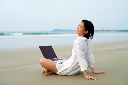 生活方式: 快樂的女孩坐在筆記本電腦在海邊工作