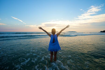 arms wide open: Girl with arms wide open at beach looking at the sunset
