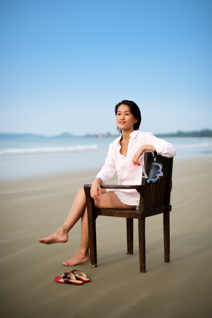 young women: Girl sitting on chair at beach doing vacation Stock Photo