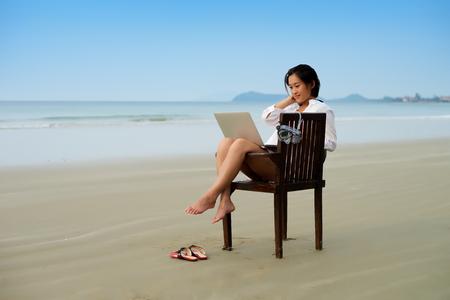 Mädchen sitzt auf dem Stuhl mit Laptop