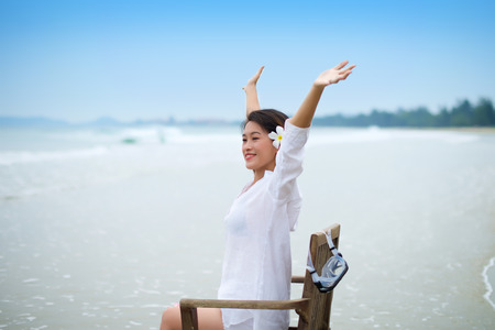 arms wide open: Girl sitting with arms wide open on chair at beach doing vacation Stock Photo
