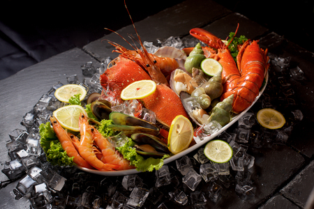 Seafood lobster plater with ice on slate