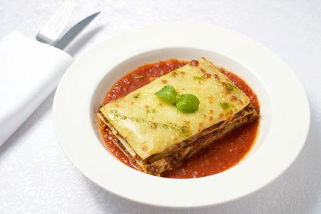 Lasagna dish on white plate Фото со стока