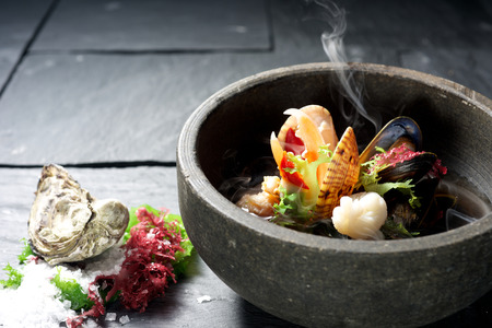 Seafood dish bowl presented on slate with ingredients